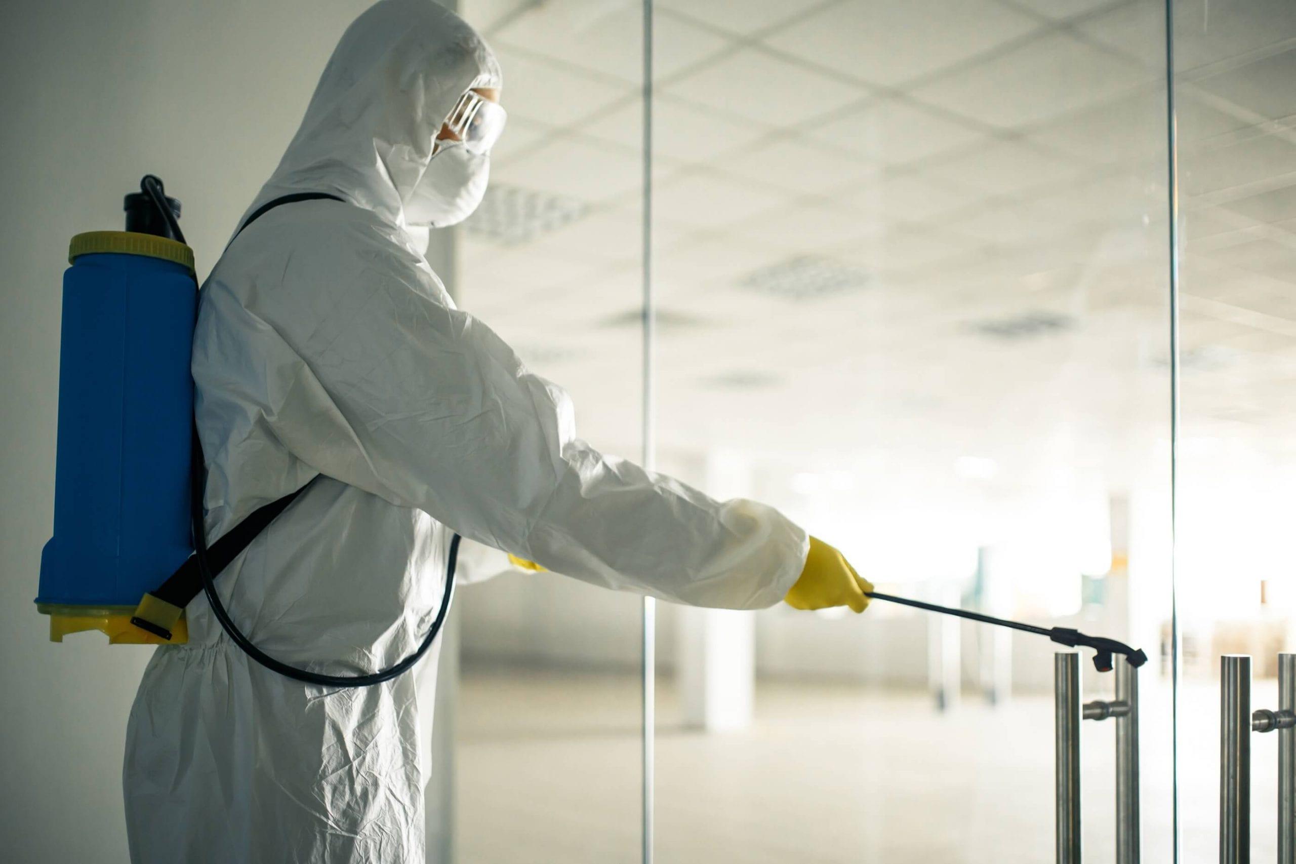 Professional cleaner in sanitation suit spraying sanitation solution on business door